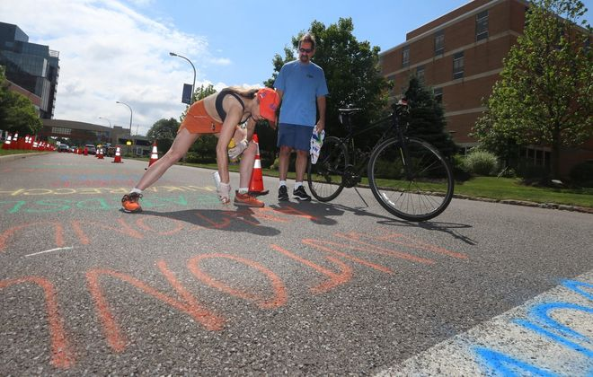 Ralph Antonucci, a cancer survivor who participated in Friday's Peloton, happened upon Ride for Roswell volunteer Justine Jopp as she was about to paint Antonucci's name on the street, outside the Roswell Park Comprehensive Cancer Center. (John Hickey/Buffalo News)