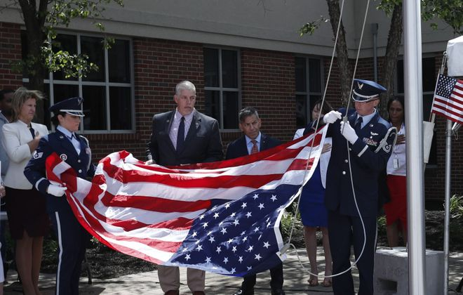 On Flag Day, HSBC employees dedicated a new flagpole at the HSBC complex in Depew. Honor guard Staff Sgt. Christina Chapman (left) and Tech Sgt. Ryan Lanighan, from the Air Reserve 914th in Niagara Falls, raise the flag. (Sharon Cantillon/Buffalo News)