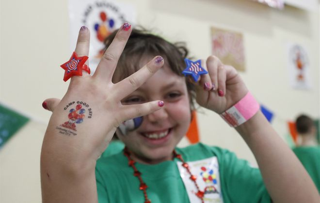 Bella Phelan shows off two of the many prizes she picked out at the Junior Camp Good Days carnival, one a ring for herself and the other a ring for her sister Peyton. Peyton was the donor for Bella's bone marrow transplant. (Sharon Cantillon/Buffalo News)