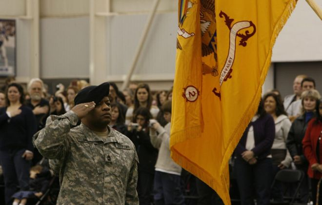 Army National Guard soldier Edwin Garris salutes with members of the 2nd Squadron 101st Cavalry during a mobilization ceremony prior to their deployment to Afghanistan in 2008. (Harry Scull Jr./News file photo)