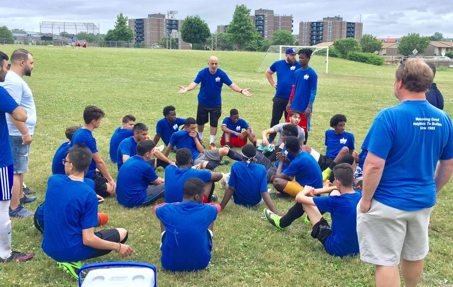 Coach Farouk Majeed, with arms spread, talks to his Journey's End refugee team at halftime of the 2018 World Refugee Day round-robin game. (Ben Tsujimoto/News file photo)