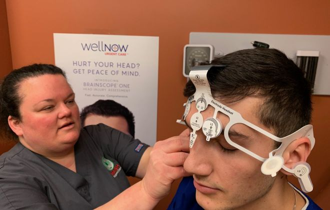Julie Green, left, site manager, and physician assistant Kyle Violanti  demonstrate how a BrainScope EEG is conducted in the Southwestern Boulevard office at WellNow Urgent Care in Orchard Park. (Scott Scanlon/Buffalo News)