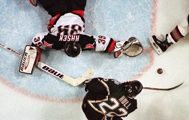 With one skate in the crease, Stars right wing Brett Hull shoots the Stanley Cup-winning goal past sprawling Sabres goalie Dominik Hasek in the third overtime period of Game 6 of the Stanley Cup Final early Sunday morning June 20, 1999. (AP Photo/Gene Puskar)