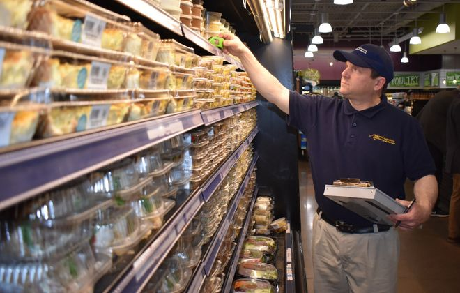 New York State Department of Agriculture and Markets food inspector John Arnold performs an inspection for proper handling and storage of food. (Photo courtesy of NYS Ag and Markets)