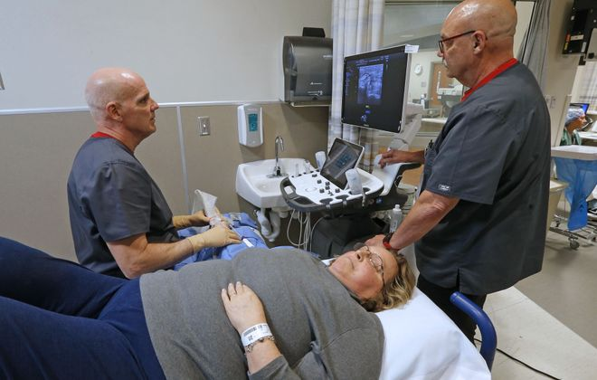 Dr. Paul Paterson, left, watches a monitor on the Samsung Ultrasound RS80 unit as a transducer shows an ultrasound image of the troubled nerve area in the wrist of patient Amy O'Connell, of Silver Creek, during surgery April 30 at the Ambulatory Care Center on the Erie County Medical Center campus. Licensed practical nurse  Patrick Nigh assisted in the procedure, which lasted about 4 minutes.   (Robert Kirkham/Buffalo News)