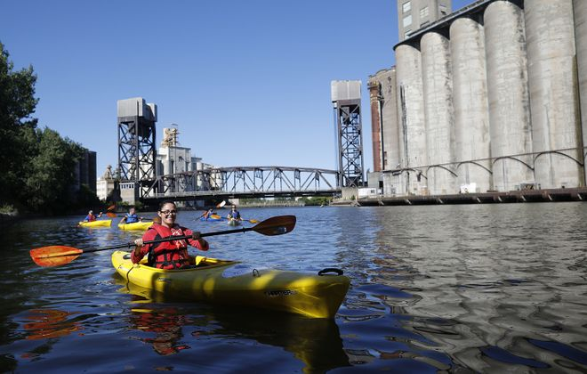 """Jordan Hawkins, a community engagement specialist for the Western New York Land Conservancy paddles in """"Elevator Alley"""" in the Buffalo River during a kayak tour on Aug. 10. The event was hosted by the  land conservancy in partnership with the Buffalo Niagara Waterkeeper. (Derek Gee/Buffalo News)"""