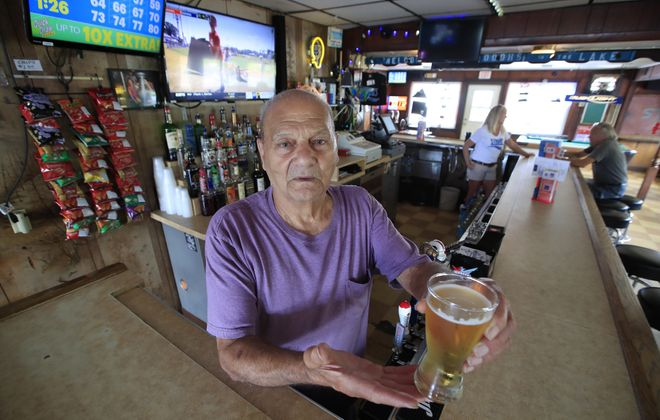 George Salim, a bartender at Stroh's since 1967, holds a cold draft beer. (Harry Scull Jr./Buffalo News)