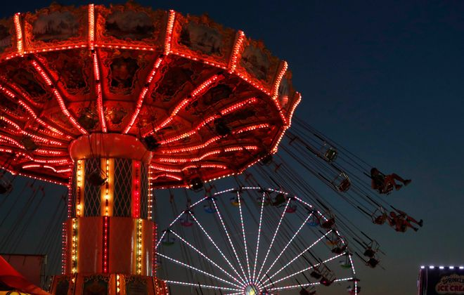 Riders enjoy the Erie County Fair's swing ride at night. (Sharon Cantillon/Buffalo News)