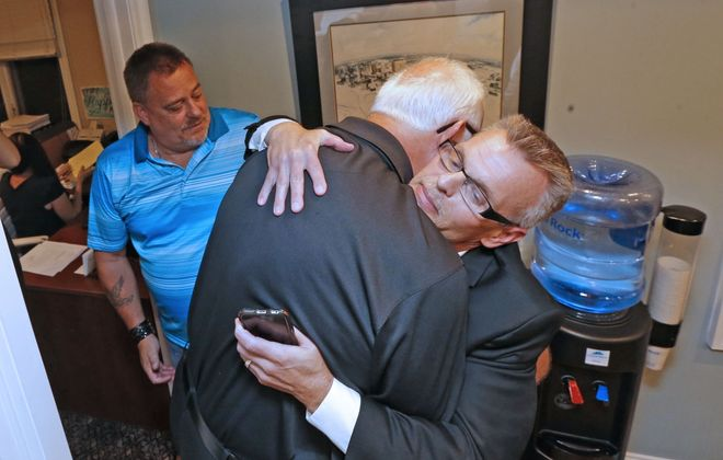 Michael Whalen, left, looks on as fellow sex abuse survivors Gary Astridge, center, and Kevin Koscielniak embrace after filing lawsuits under the Child Victims Act in August. To recover lost support among parishioners, the diocese must be entirely forthcoming about what happened, even if the cases end up in bankruptcy court. (Robert Kirkham/Buffalo News)