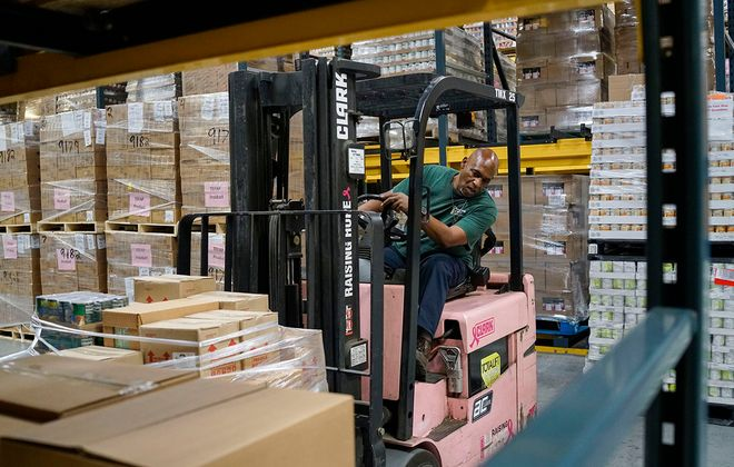 Timothy Kuhn, safety and food processing coordinator at FeedMore WNY, moves a pallet of food for shipment to a local pantry at the food bank distribution center, (Derek Gee/News file photo)