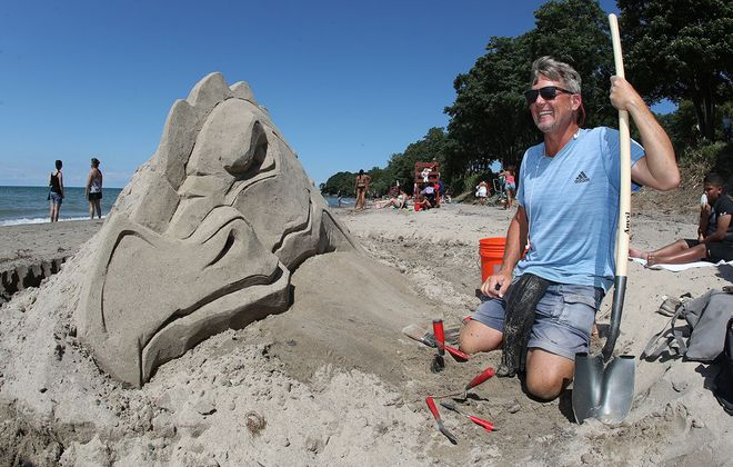 Dan Belcher, a nationally known sand sculptor, created a dragon Sunday at Wright Park Beach in Dunkirk. (James P. McCoy/Buffalo News)