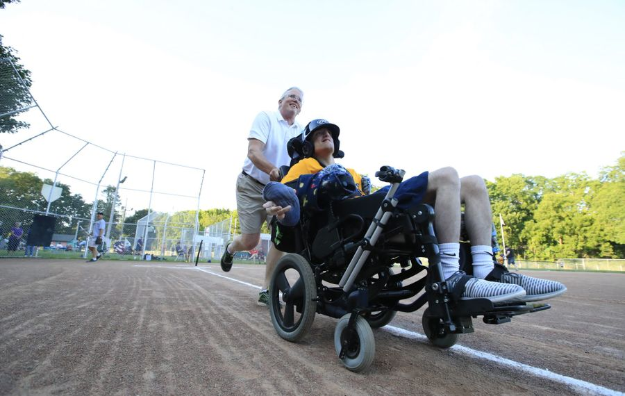 Rory O'Connor, an Orchard Park man born with cerebral palsy, and his father Mike hurry toward first base in an Aktion Club baseball game in East Aurora at the Aurora Community Pool Park baseball diamonds. (Harry Scull Jr./Buffalo News)