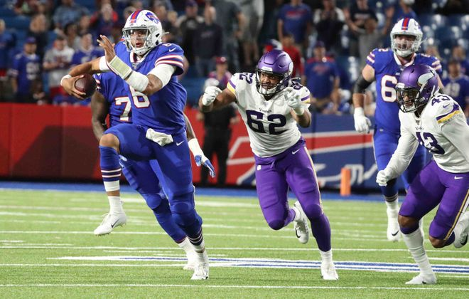 Bills quarterback Tyree Jackson rushes for a first down against Minnesota Vikings defensive end Anree Saint-Amour. (James P. McCoy/News file photo)