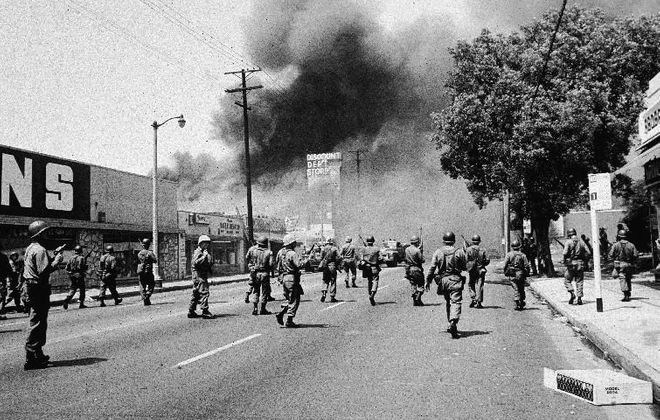 Armed National Guardsmen march toward smoke on the horizon during the street fires of the Watts riots, Los Angeles, California, August 1965. (Getty Images)
