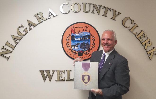 Joseph A. Jastrzemski displays the county's official book of Purple Heart recipients on Tuesday, Aug. 6, 2019. (Thomas J. Prohaska/Buffalo News)