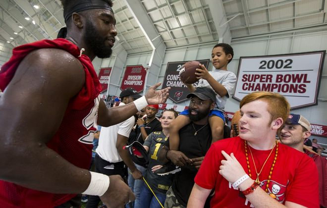 Tampa Bay Buccaneers linebacker Demone Harris hands Jordan McDuffie, 5, a football after autographing it. (Monica Herndon, Tampa Bay Times)