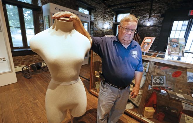 Doug Larkin, president of the Town of Clarence Historical Society, stands by the mannequin that used to display the stolen wedding dress. (Robert Kirkham/Buffalo News)