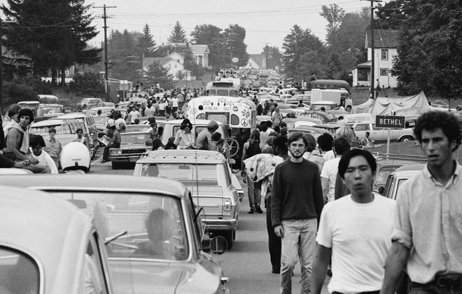 People walk along roads choked with traffic on the way to Woodstock in Bethel in August 1969. (Photo by Hulton Archive/Getty Images)