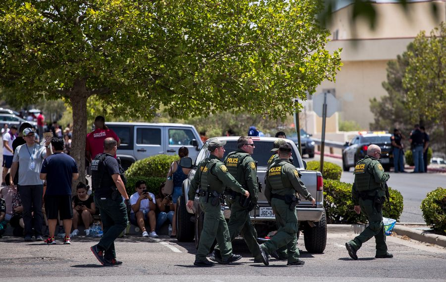Customs and Border Patrol police walk past people who were evacuated from Cielo Vista Mall and a Walmart where 20 people were killed and 26 wounded  Saturday in El Paso, Texas. (Joel Angel Juarez/AFP/Getty Images/TNS)