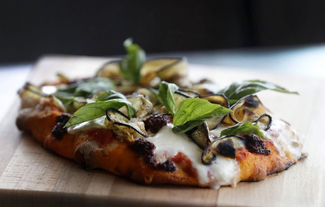 Daniela crafts a style of pizza called the pinsa, such as this Nduja and eggplant pinsa. (Mark Mulville/Buffalo News)
