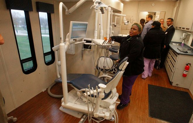 Bennette Burt, a dental assistant in the University at Buffalo School of Dental Medicine, looks over the dental station on the S-Miles to Go mobile dental clinic. The clinic has served the community for more than 15 years,, providing more than 38,000 patient visits. (John Hickey/News file photo)