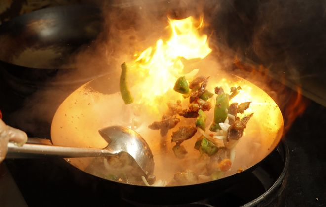 In Tonawanda, Qutoom chef Mohammed Shofiq prepares the lamb sizzler in a wok. (Sharon Cantillon/Buffalo News)