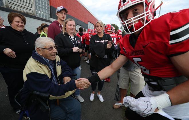 Larry Schalberg, who graduated in 1946 from Lancaster High School, shakes hands with senior defensive back Ethan Jurkowski prior to the start of the 100th season opener in Lancaster football history. Jurkowski returned the game's opening kickoff for a touchdown during the Legends' 51-6 rout of Hutch-Tech. (James P. McCoy/Buffalo News)