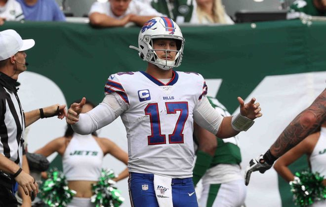 Bills quarterback Josh Allen celebrates after rushing for a touchdown over New York Jets defensive end Henry Anderson in the fourth quarter  (James P. McCoy/Buffalo News)