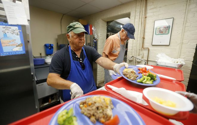 Peter Amodeo, left, and Sal Lazzaro serve lunch at Friends of Night People on Hudson Street. The group offers hot meals and other assistance to those who need it. (Mark Mulville/Buffalo News)