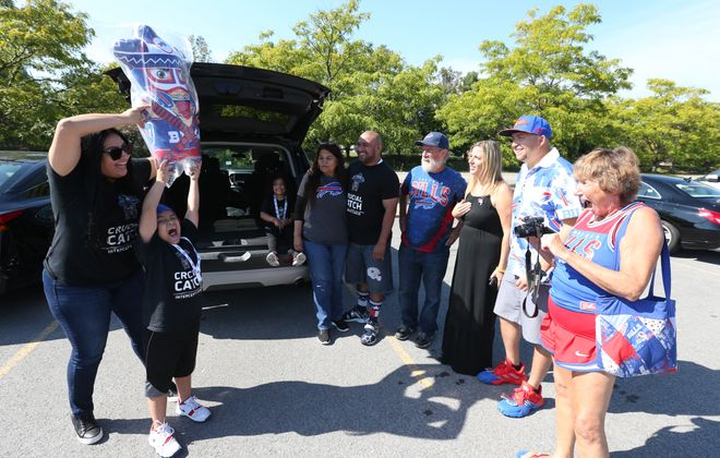"""Veronica Borjon and her son Gino Castro 7, brought a large doll in the likeness of Ezra Castro (Pancho Billa) from Texas  that will be raffled off Saturday at the memorial for the Bills superfan at New Era Field's Hammer lot. In the van is Borjon's daughter Loulu; to her left are Ken """"Pinto"""" Ron Johnson and Kristin Ruesch,two of the organizers of the memorial, and fellow Bills loyalists Andrew Arreguy of Texas and Joanie DeKoker of greater Syracuse. (James P. McCoy/Buffalo News)"""