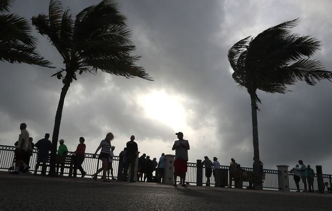 People stand at the water's edge of the Atlantic Ocean as winds from Hurricane Dorian pick up on Sept. 2, 2019, in Vero Beach, Fla. The category 5 storm has come to a standstill, parking itself over Grand Bahama Island and unleashing blinding rain, powerful winds and a destructive storm surge but largely sparing the Florida coast for the time being. (Mark Wilson/Getty Images)