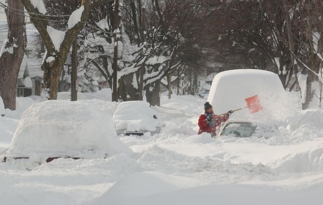 A woman digs her car out on Edgewood Street in South Buffalo on Dec. 27, 2001. (News file photo)