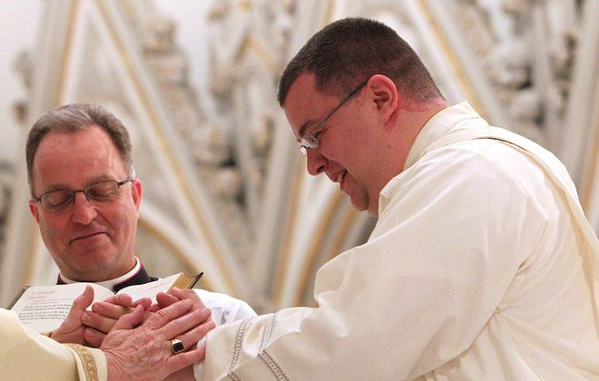 Jeffrey Nowak, right, is ordained into the priesthood on June 2, 2012, as Msgr. David LiPuma watches. (Sharon Cantillon/News file phtoo)