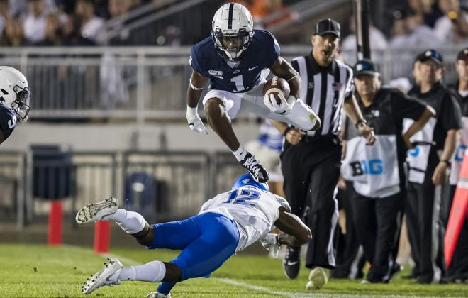 Penn State's KJ Hamler hurdles UB's Devon Russell during the first half Saturday in State College, Pa.  (Scott Taetsch/Getty Images)