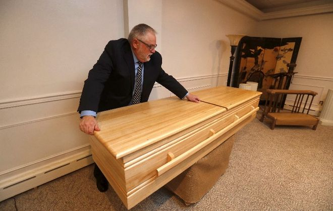 Gregory Wood of the Wattengel Funeral Home in North Tonawanda recommends a pine casket for a green funeral.  (Mark Mulville/Buffalo News)