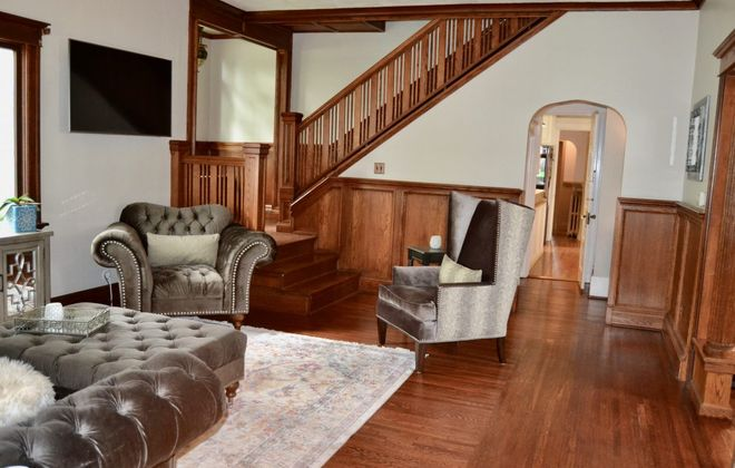 The living room and staircase in this 19th-century City of Tonawanda home. (Photos courtesy Samantha Muscato)