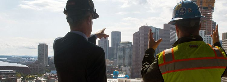 Charlie Jacobs of Delaware North speaks with construction  superintendent Mike Carrucci looking out at downtown Boston from what will be the 15th floor reception area of Verizon's new innovation center at Hub on Causeway, the mixed-use development in the footprint of the old Boston Garden Tuesday Sept. 10, 2019. (Neal Hamberg)