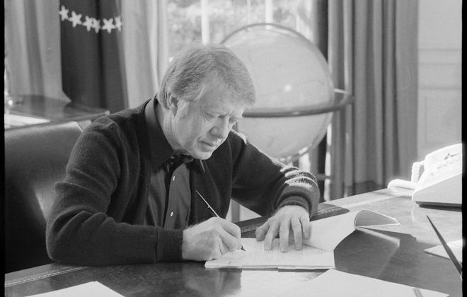 President Jimmy Carter works at his desk in the White House (National Archives and Records Administration).