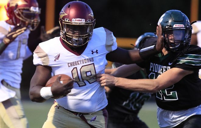 Cheektowga quarterback Aaron Smith stiff arms Pioneer defender Gabe Fisher during the first half of the Warriors' victory Friday night. (Harry Scull Jr./The Buffalo News)