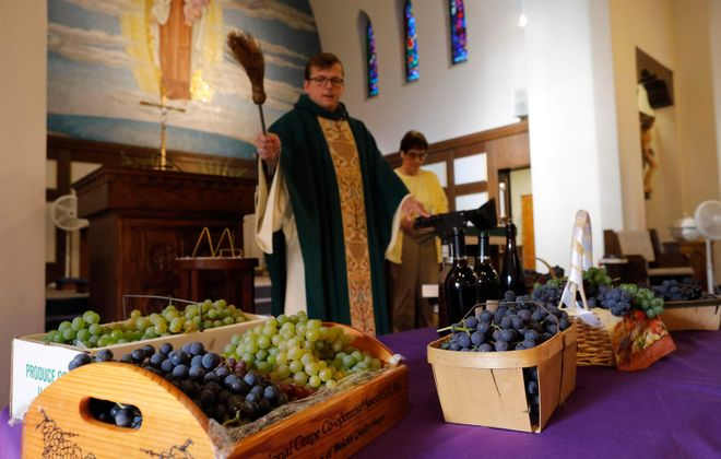 Inspired by a European tradition, the Rev. Daniel Fiebelkorn performs a blessing of the grapes during mass at Our Lady of Mount Carmel Catholic Church in Silver Creek on Tuesday, Sept. 17, 2019.  (Derek Gee/Buffalo News)
