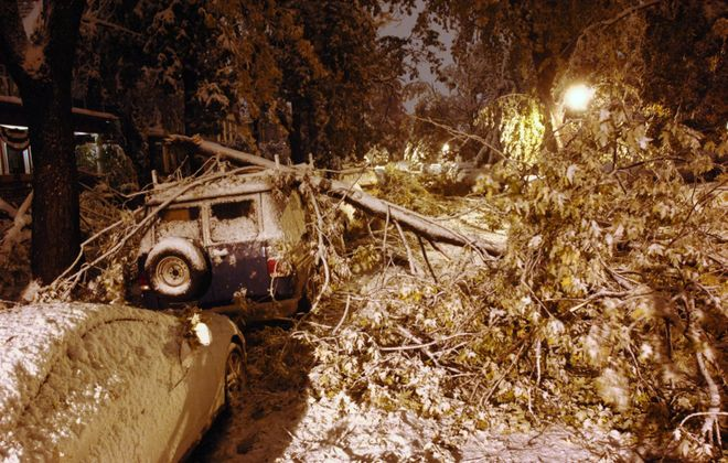 A large tree limb rests on top of a van and blocks Ashland Avenue after a bizarre October snowstorm Oct. 12, 2006. (Derek Gee/Buffalo News)