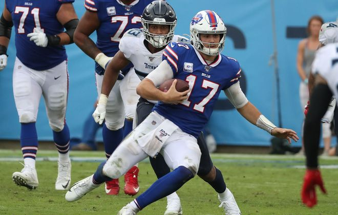 Bills quarterback Josh Allen rushes for a first down over Titans outside linebacker Kamalei. (James P. McCoy/Buffalo News)