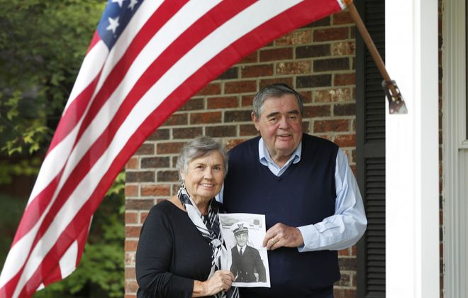 """Peggy Crotty Kelly and her brother, Patrick Crotty, hold a photo of their uncle, Lt. Thomas """"Jimmy"""" Crotty, at Pat's home in Orchard Park.   (Mark Mulville/Buffalo News)"""