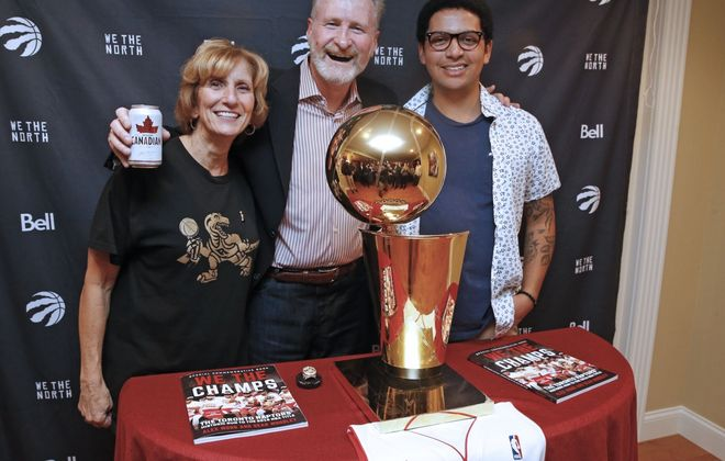 Former Niagara University head basketball coach Jack Armstrong, center, with his wife, Dena, and his oldest son, Kevin, pose in their dining room with the NBA champion Toronto Raptors' Larry O'Brien Trophy on Tuesday, Oct. 29, 2019. (Robert Kirkham/Buffalo News)