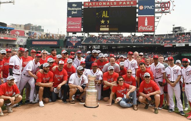 With Capitals captain Alex Ovechkin and Nationals manager Davey Martinez directly behind the Stanley Cup, the Caps and Nats posed for a picture at Nats Park as the teams celebrated Washington's first Cup title on June 9, 2018. (Getty Images)