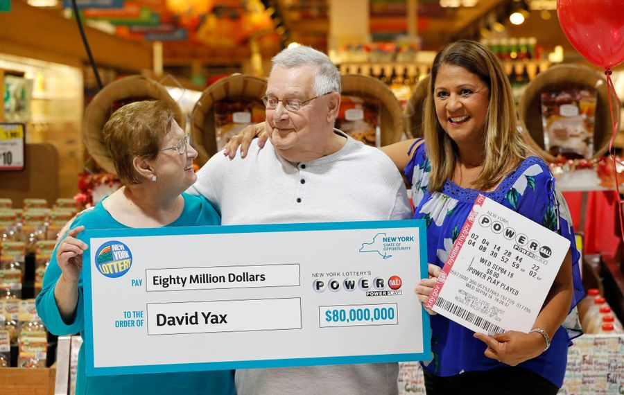 David Yax, center, is presented with a ceremonial $80 million check as he is introduced by Yolanda Vega of the New York Lottery as the first Powerball winner in Western New York on Tuesday, Oct. 22, 2019. With Yax, on left, is his wife Claudia. (Mark Mulville/Buffalo News)