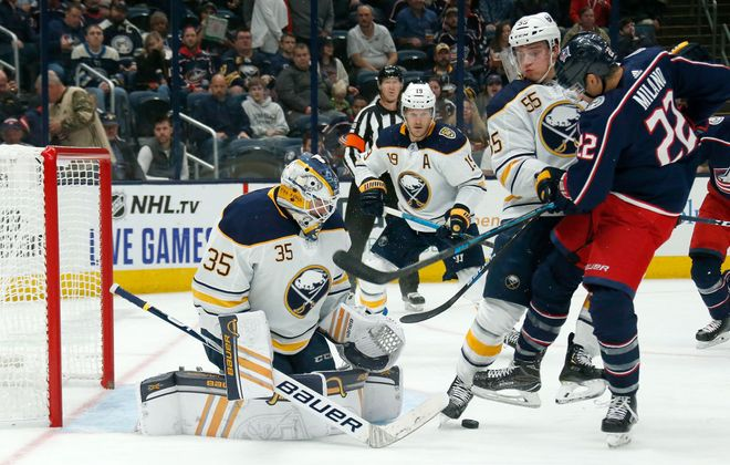 Linus Ullmark makes a save on Columbus' Sonny Milano as Jake McCabe and Rasmus Ristolainen work the front of the net (Getty Images).