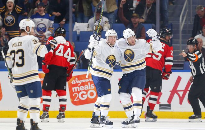 Kyle Okposo pumps his fist to celebrate his second-period goal as Johan Larsson joins in (Mark Mulville/Buffalo News).