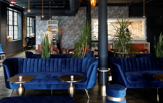 At Waxlight Bar a Vin, blue velvet and plants soften industrial space edges. (Derek Gee/Buffalo News)