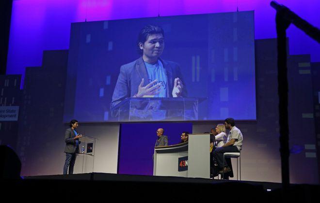 Ravi Sahu, left, presents his award-winning pitch to the judges at the 43North finals. (Robert Kirkham/Buffalo News)